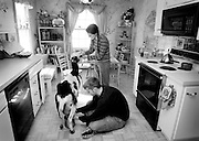 Josh Brown milks their goat, Kali, in the kitchen while wife Sarah helps out. The couple often milk their goats inside the kitchen because they say the goats are less distracted there. The couple lives a simple life without TV.