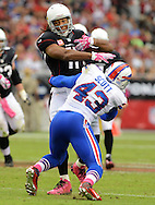Oct. 14, 2012; Glendale, AZ, USA;  Arizona Cardinals wide receiver Larry Fitzgerald (11) is tackled by Buffalo Bills linebacker Bryan Scott (43) during the game at University of Phoenix Stadium. The Bills defeated the Cardinals 19-16 in overtime. Mandatory Credit: Jennifer Stewart-US PRESSWIRE..