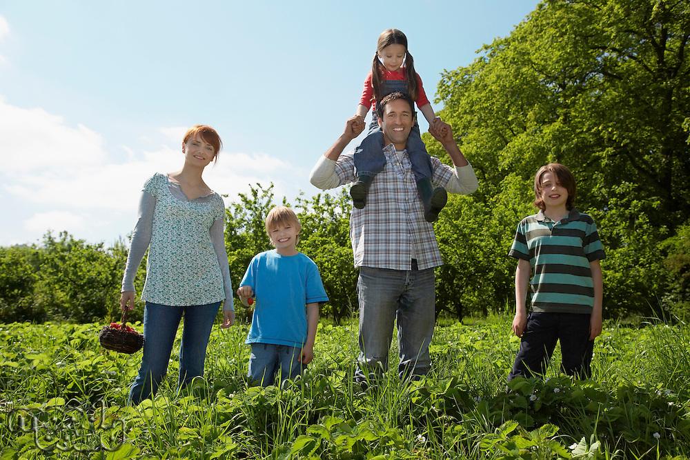 Parents and children (5-9) in strawberry field portrait