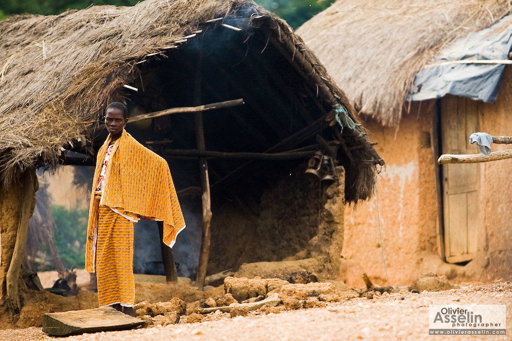 A woman stands outside her home in Tano Akakro, Cote d'Ivoire on Saturday June 20, 2009.