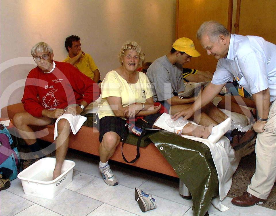 """nijmegen 4 daagse dr Bosch uit Ermelo is al 14 jaar als arts verbonden (vrijwillig) aan het rode kruis op de foto helpt hij wee verscheidene """"patienten"""" met hun typische vierdaagse problemen..fotoburo frank uijlenbroek©henk offenberg"""