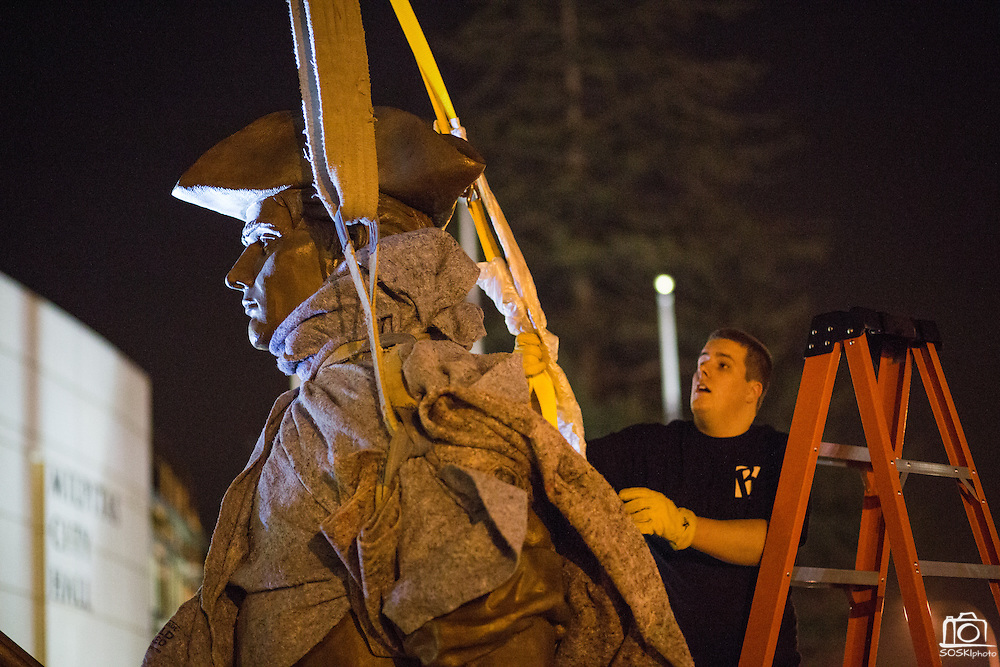 Dylan Moses of Baer Bronze Fine Art Foundry attaches ratchet straps to the 12-foot Milpitas Minute Man sculpture to lift it into place with a crane, outside Milpitas City Hall in Milpitas, California, on January 24, 2014.  The sculpture was created by David Alan Clark, took 10 months to complete, and weighs approximately 2,500 pounds. (Stan Olszewski/SOSKIphoto)