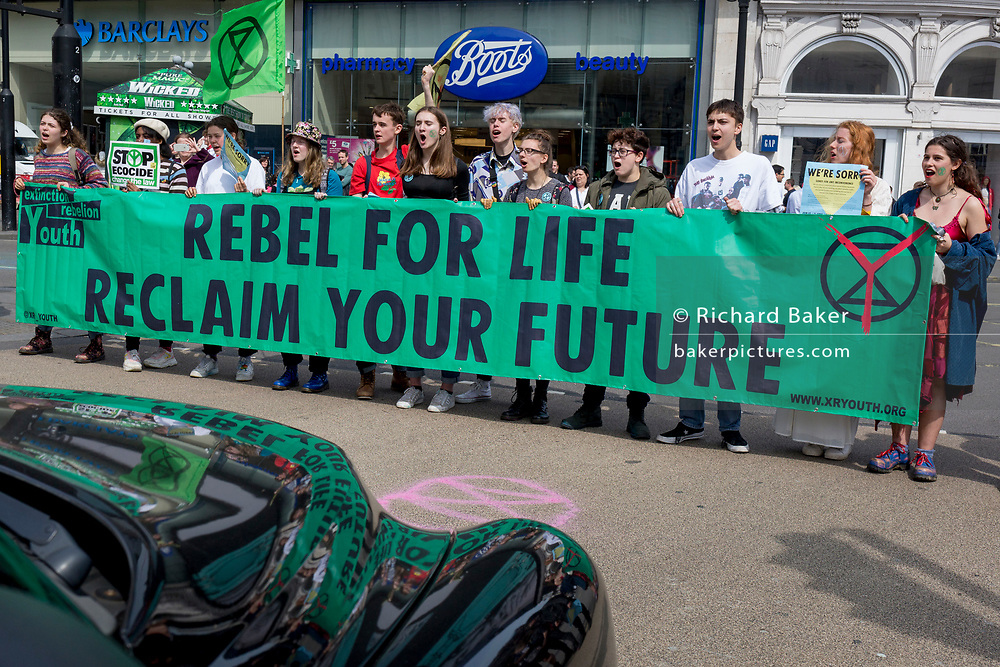 Beneath advertising, young campaigners block a black cab stopped in Piccadilly Circus on day 4 of protests by climate change environmental activists with pressure group Extinction Rebellion, on18th April 2019, in London, England.