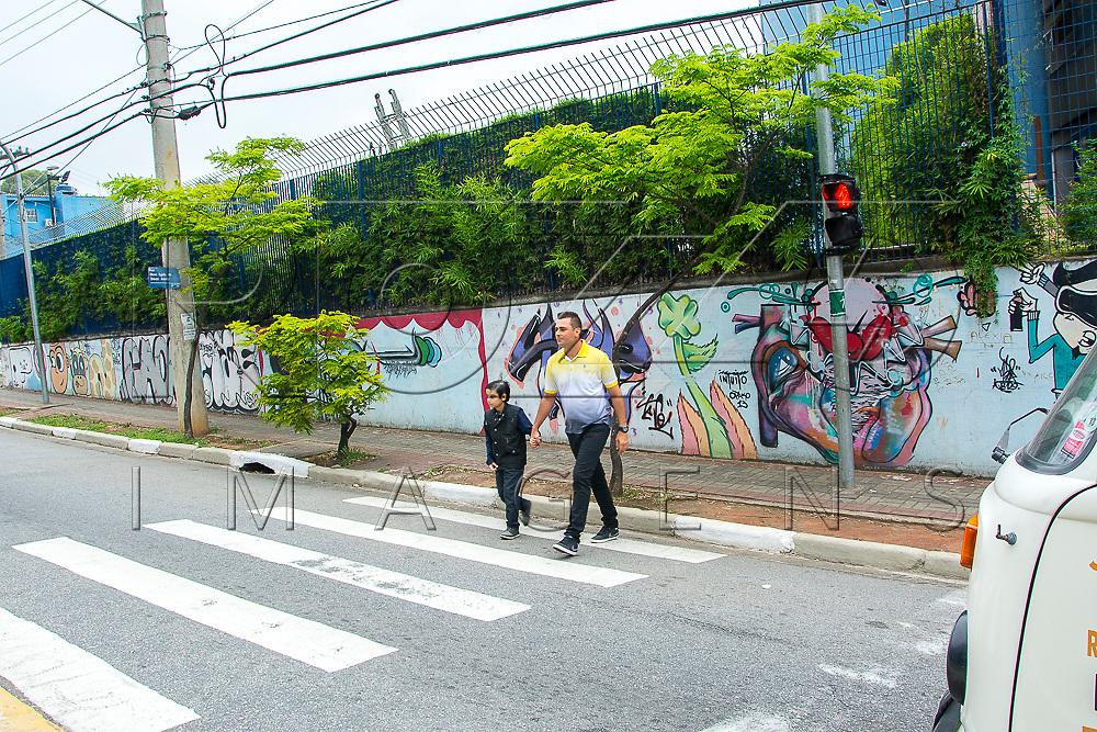 Adulto segurando a mão de uma criança ao atravessar a rua na faixa de pedestres, São Paulo - SP, 09/2016. Uso de imagem autorizado