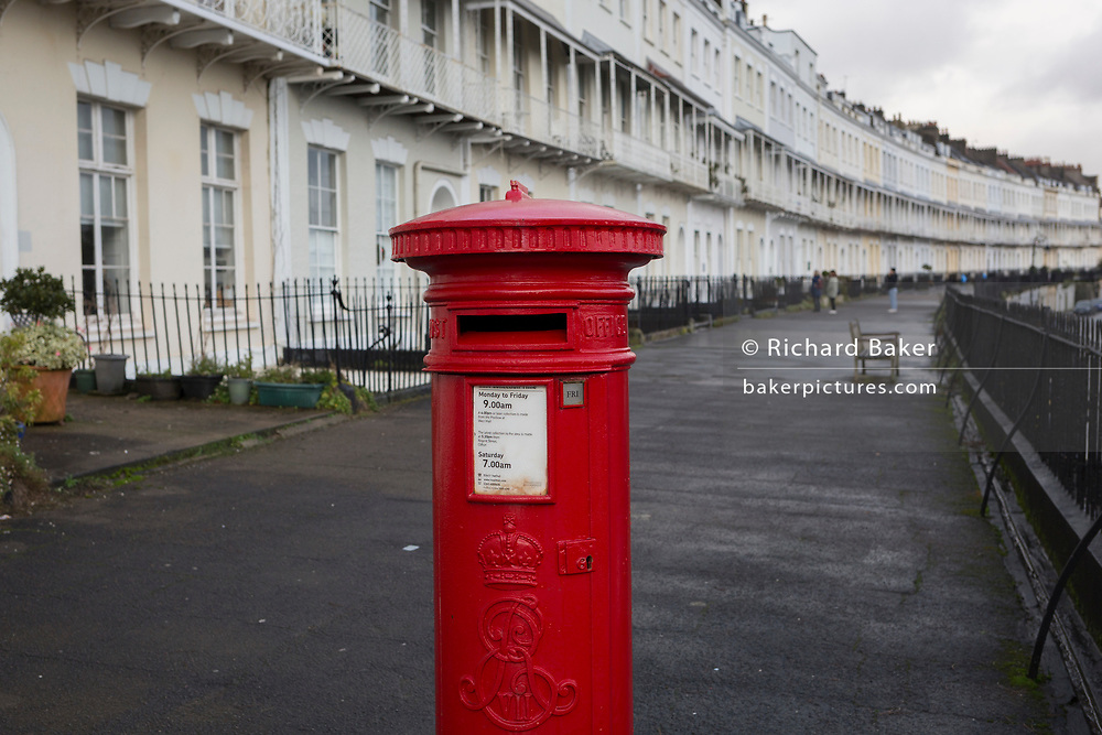 A Royal Mail postal box and a background of terraced homes on Royal York Crescent, on 26th December 2019, in Clifton, Bristol, England.