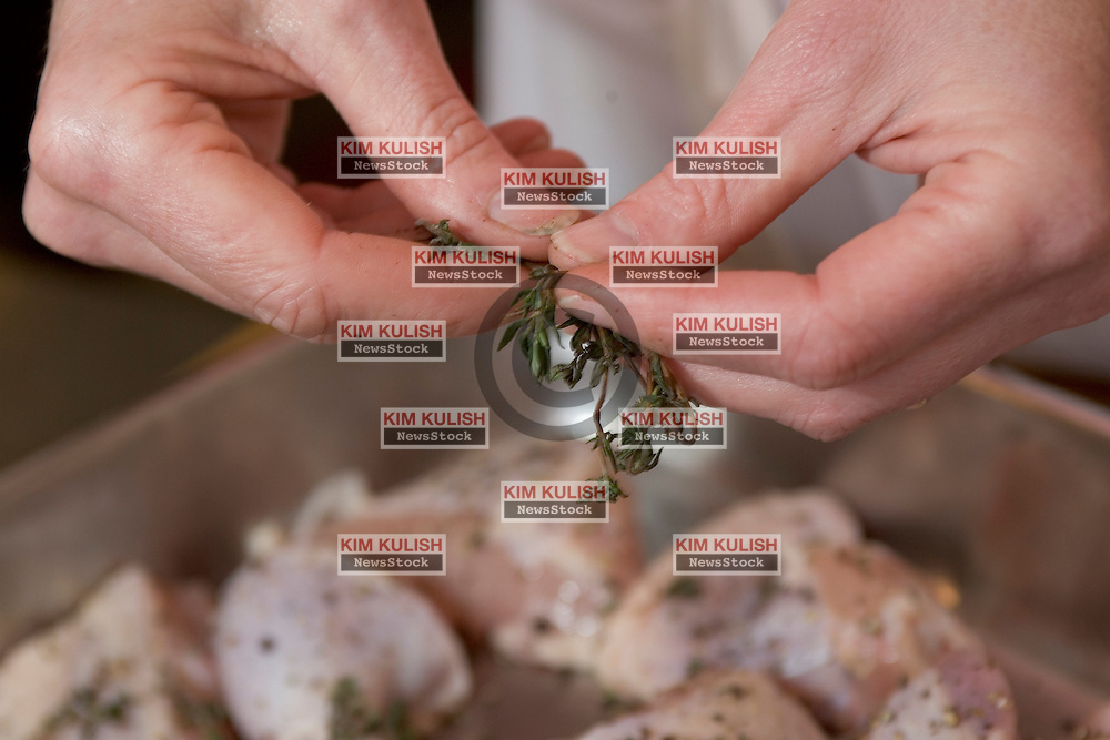Judy Rodgers, chef , founder  of the Zuni Cafe  in San Francisco and author of a popular cookbook with her recipes NOTE THIS IS A FRIED CHICKEN RECIPE:  step 2--Season cut chicken with herbs.  Photo by Kim Kulish
