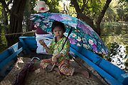 sheltering under the umbrella while her mother  rows the boat.  Mangrove swamp, Tonle Sap, Cambodia.