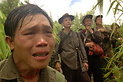 As we approached the site of the April 6th massacre one soldier, Song Yee Thao, screamed and began to cry, then many of the others joined in mourning, near Vang Vieng, Laos, June 30, 2006.  Group leader, Blia Shoua Her, in background...**EXCLUSIVE, no tabloids without permission**  .Pictured are a group of Hmong people who report an attack against them April 6, 2006 by Lao and Vietnamese military forces.  26 people perished, 5 were injured, and 5 babies died shortly after because their dead mothers could not breast-feed them.  Only one adult male was killed, the other 25 victims were women and children (17 children).  The Lao Spokesman for the Ministry of Foreign Affairs says this is a fabrication, an investigation has been completed, and there was no attack.  The Hmong group says no officials have interviewed witnesses or visited the crime scene, a point the Lao Spokesman did not deny.  ..The Hmong people pictured have hidden in remote mountains of Laos for more than 30 years, afraid to come out.  At least 12,000 are said to exist, with little food, scavenging in the jungle. Most have not seen the modern world.  Since 1975, under the communists, thousands of reports evidence the Hmong have suffered frequent persecution, torture, mass executions, imprisonment, and possible chemical weapons attacks.  Reports of these atrocities continue to this day.  The Lao Government generally denies the jungle people exist or that any of this is happening.  The Hmong group leader, Blia Shoua Her, says they are not part of the Hmong resistance and want peace.  He claims they are just civilians defending their families, hoping to surrender to the UN..