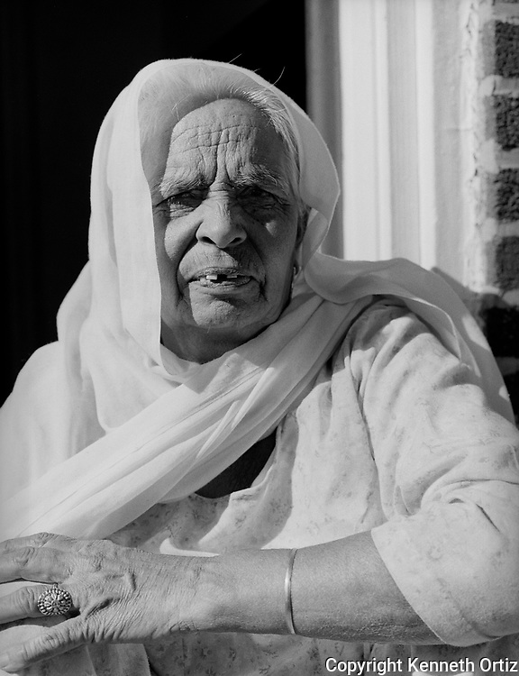 An Indian Grandmother sits in front of her stoop in Woodside Queens, New York.