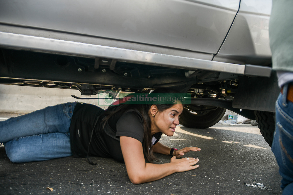 April 30, 2019 - Caracas, Miranda, Venezuela - A woman is seen hiding under a car to avoid bullets. The Venezuelan opposition leader has called for the military to rise up against the President on Tuesday. (Credit Image: © Roman Camacho/SOPA Images via ZUMA Wire)