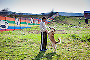 Teenager Dusan is playing with his dog Bielku beside the wall on the side of the Roma settlement in Ostrovany. The village of Ostrovany, located about 50 km from Kosice, shows the difficulties experienced by the minority and majority population living together in the one community. A wall was erected in 2009 to divide private properties from the neighbouring Roma settlement.