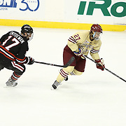 Quinn Smith #27 of the Boston College Eagles keeps the puck from Torin Snyderman #17 of the Northeastern Huskies during The Beanpot Championship Game at TD Garden on February 10, 2014 in Boston, Massachusetts. (Photo by Elan Kawesch)