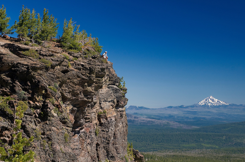 (m) Hiker sitting at Tam McArthur Rim with view to Cascade Mountain Range, Three Sisters Wilderness, Deschutes National Forest, Cascade Mountain Range, near Sisters, Central Oregon, Oregon, USA.