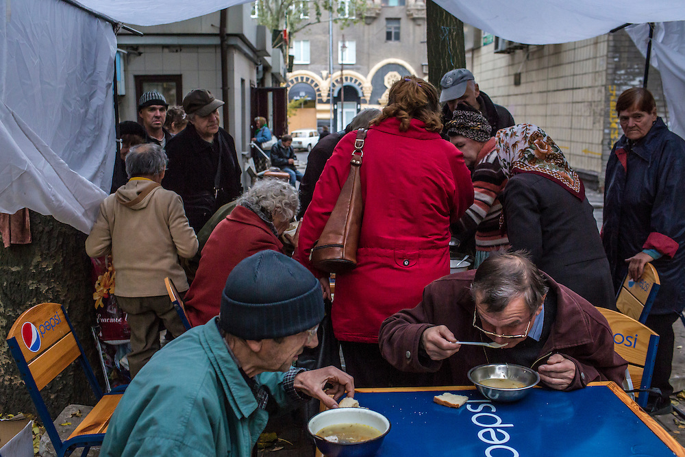 People in need of a free meal eat soup on Thursday, October 16, 2014 in Donetsk, Ukraine. Many older residents have not received pension payments in months and no longer have enough money to buy food. Photo by Brendan Hoffman, Freelance