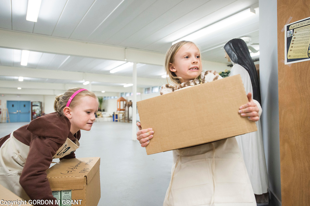 Ryder Stella, 6, left, and Jaya Lumi, 7, members of the non-profit Camp SoulGrow, help to stock food at the Montauk Food Pantry at St. Therese Church in Montauk, March 14, 2016.