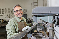 Portrait of a happy mature man wearing protective eyewear standing by machinery in workshop
