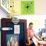 "The film adaptation of Cheryl Strayed's memoir, ""Wild,"" stars Reese Witherspoon as a troubled woman who challenges herself by hiking the Pacific Crest Trail in Oregon. Cascade Locks, Ore., marks the northern end of the trail at the Columbia River, where Strayed ended her hike and celebrated with an enormous soft-serve ice cream cone at the East Wind Drive-In. Here Melissa Johnson closes the walk-in freezer beneath a PCT banner."