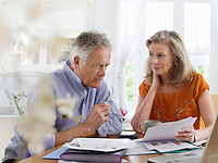Senior couple looking at bills sitting at dining table