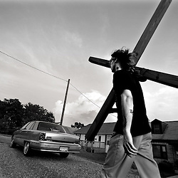 """Jeromy Boyd hoist the 12-foot cross and heads down Memorial Avenue, his sneakers slapping the pavement. He prays quietly along the way. A small wheel stops the miles from grinding way the base of his wooden cross. """"For most Christians I've seen, it's all about the talk and no walk,"""" he says. God told him to stop in Roanoke, after drugs, after homelessness, after three years as a street minister. His 100-pound cross is heavy, especially after trading the dusty flatlands of Texas for the humid hills of Virginia. His hips and back ache. His knees throb. After being challenged about his purpose by a passerby, Jeromy replies, """"I'm not Jesus. I'm just trying to spread his message."""""""