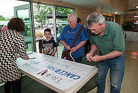 Communications Associate Sarah Lapointe assists Cameron Bean and his grandmother Jenny Judd (1 1/2 yrs) and Pat Tierney (3 yrs) as they sign the banner for LRGH Cancer Survivor Day on Tuesday afternoon.    (Karen Bobotas/for the Laconia Daily Sun)