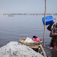 Un homme se rince à l'eau douce pour s'enlever le sel collé à sa peau.