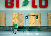 Josh Sweat, a butcher at the BiLo grocery store, moves a shopping cart return rack during storm preparations for Hurricane Matthew, Thursday, Oct. 6, 2016, in Darien, Ga. (AP Photo/Stephen B. Morton)
