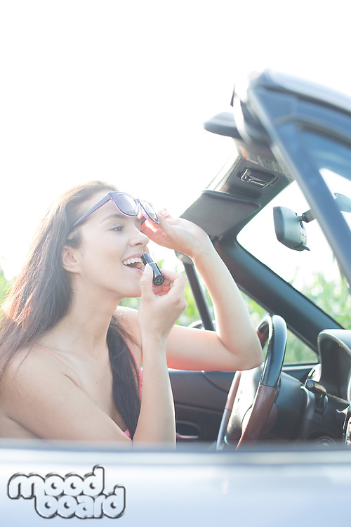 Woman holding sunglasses applying lipstick in convertible on sunny day
