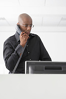 Office worker standing in office using telephone
