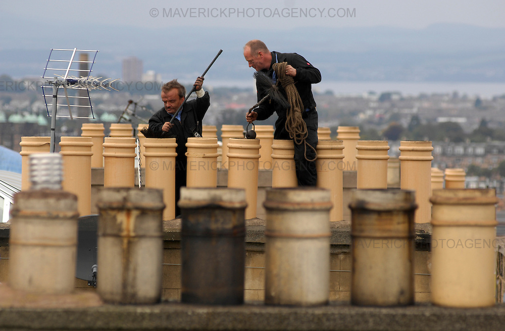 Feature on Chimney Sweeps. Pictured Kirk McLenaghan (short hair) and Bert Boat from Auld Reekie chimney sweeps cleaning chimneys on the roof of a block of flats in Viewforth.