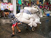 30 MAY 2013 - BANGKOK, THAILAND:  A porter delivers clothes to a market stall in Bobae Market in Bangkok. Bobae Market is a 30 year old famous for fashion wholesale and is now very popular with exporters from around the world. Bobae Tower is next to the market and  advertises itself as having 1,300 stalls under one roof and claims to be the largest garment wholesale center in Thailand.      PHOTO BY JACK KURTZ