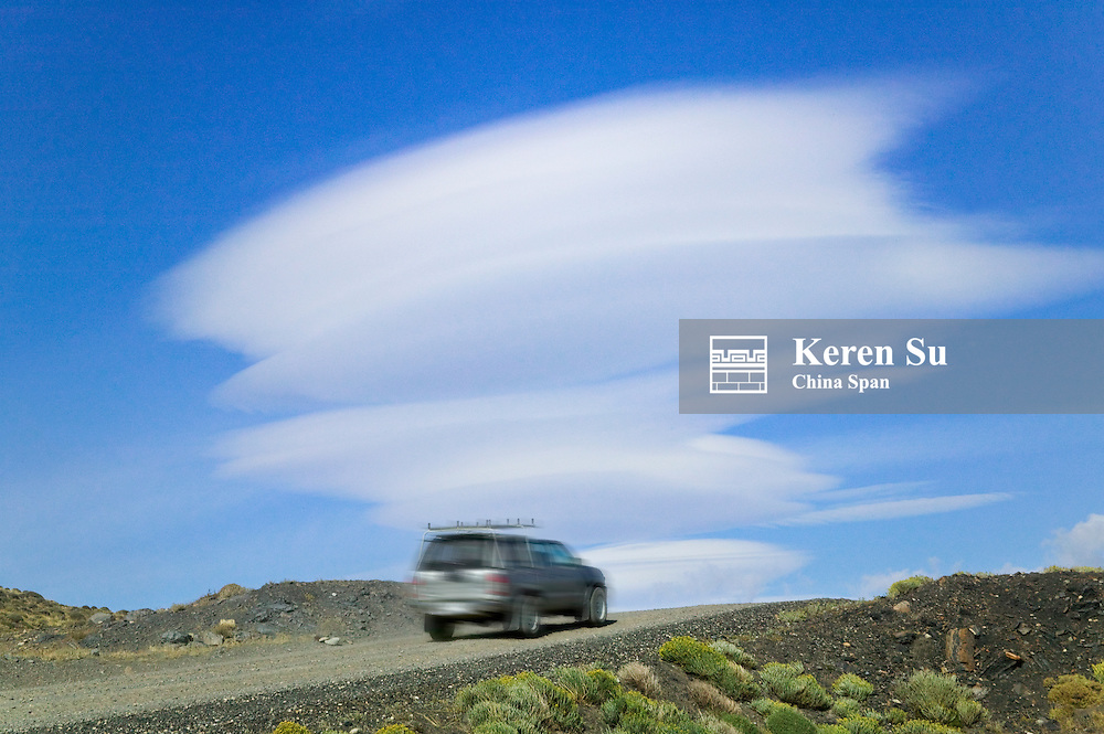 A jeep on the road in the mountain, dramatic clouds in the blue sky, Torres del Paine National Park, Patagonia, Chile