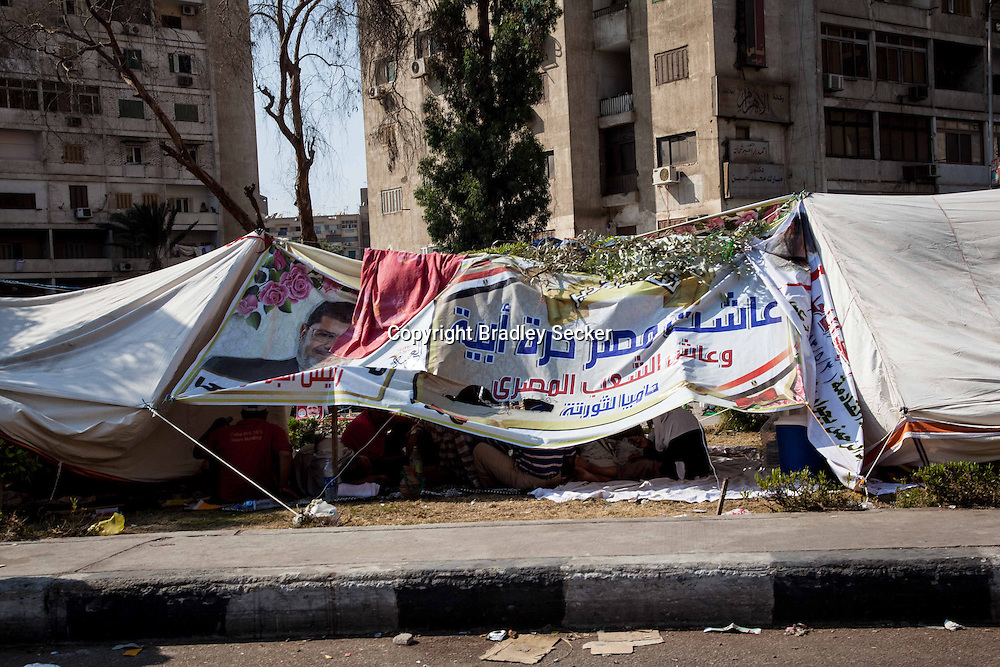 During the heat, people take shelter in tents and under banners supporting Mohammed Morsi in Nassr City, Cairo