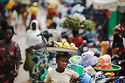 A girl carries a plate of apples for sale on her head as she walks through the market in the town of Kayes, Mali on Thursday September 2, 2010.