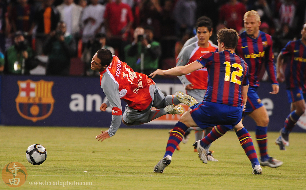 August 8, 2009; San Francisco, CA, USA; Chivas de Guadalajara forward Javier Hernandez (left) is tripped by FC Barcelona defender Andreu Fontas (12) during the second half in the Night of Champions international friendly contest at Candlestick Park. The game ended in a 1-1 tie.