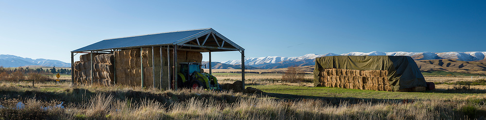 A haybarn containing a tractor and haybales next to a covered haystack. The snow capped Hawkdon Ranges are in the background.