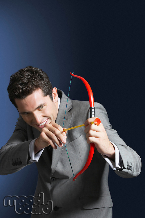Man aiming toy bow and arrow against dark background