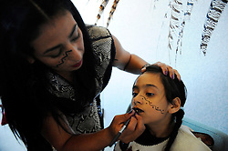 "Ehecatl Chantico Moreno (Wind and Fire of the Home) applies makeup to her daughter before a performance on September 9th, 2012 at Fiesta del Mar at the Monterey Bay Aquarium. By teaching their children traditional dances and conduct, members of the Yaocuauhtli - Eagle Warrior ""calpulli,"" or group, are preserving a proud ethnic heritage."