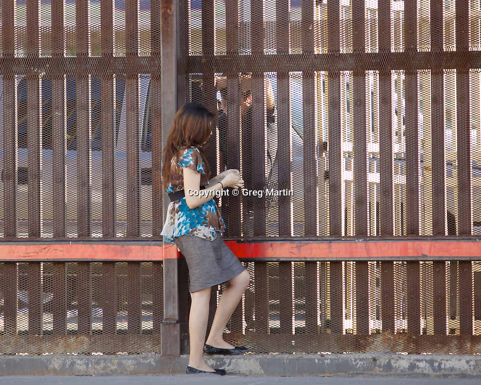 A young man and women speak through the US-Mexican border fence in Calexico, California NMR