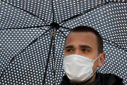 UNITED KINGDOM, London: 28 April 2020 <br /> A man wearing a mask to prevent the further spread of the coronavirus seeks shelter under his umbrella during a wet and miserable morning. The weather is set to stay wet for the next few days according to the Met Office.