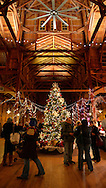 Old Bethpage, New York, USA. December 26, 2014. A large traditional 1866 decorated Christmas Tree tree is under the high ceiling of the Barn wood peg spire at night, on the historic, rustic grounds of Old Bethpage Village Restoration, transformed by candlelight and Christmas decorations into a Nineteenth Century holiday experience for Long Island visitors. Candlelight Evenings are held until December 30th.