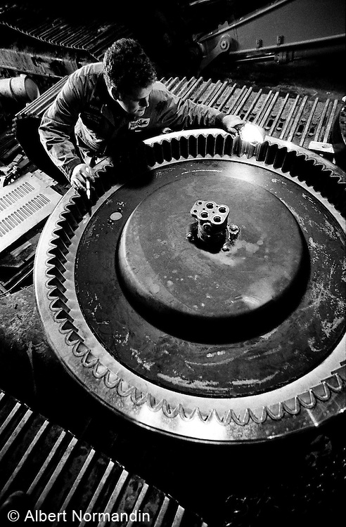 Technician servicing large ring gear for loader