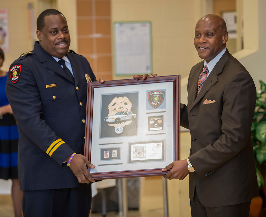 Assistant Chief Michael Benford, left, honors retired Chief Jimmy Dotson, right, during the Houston ISD Police awards banquet at Thompson Elementary School, August 15, 2014.