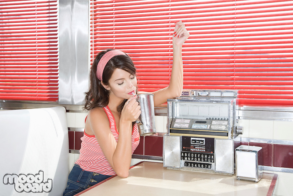 Young Woman in a Diner Booth Drinking a Shake