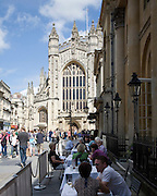 People sitting outdoors at cafe tables in the Abbey churchyard, Bath, Somerset, England