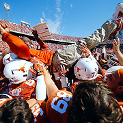Texas Longhorns players lift Texas Longhorns head coach Charlie Strong in the air during an NCAA Football regular season Red River Rivalry game against the Oklahoma Sooners on Saturday, Oct. 10, 2015 in Dallas. (Ric Tapia via AP)