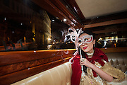 A chinese tourist woman dressed in traditional costume in a motorboat taxi in Venice during the carnival.
