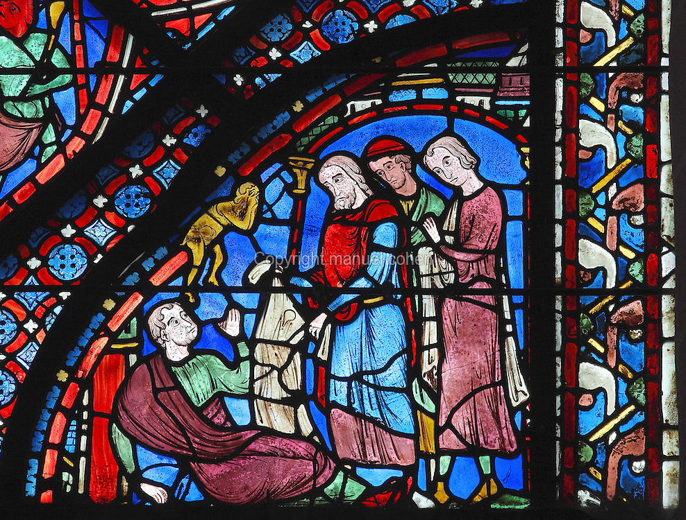St James removes his kerchief from Philetus, who immediately miraculously recovers from the magic spell of Hermogenes. The yellow demon holds his head in despair. Section of the healing of Philetus, 1210-25, from the Life of St James window in the ambulatory of Chartres Cathedral, Eure-et-Loir, France. This window tells the story of the life of St James the Greater, apostle of Jesus and son of Zebedee. It is situated next to the apostles chapel. Chartres is a stop on the pilgrimage route to Compostela, where James' relics lie. Chartres cathedral was built 1194-1250 and is a fine example of Gothic architecture. Most of its windows date from 1205-40 although a few earlier 12th century examples are also intact. It was declared a UNESCO World Heritage Site in 1979. Picture by Manuel Cohen