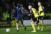 Elvis Bwomono runs past Stephen Quinn and Reece Hutchinson during the EFL Sky Bet League 1 match between Burton Albion and Southend United at the Pirelli Stadium, Burton upon Trent, England on 3 December 2019.