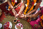 Three surrogates (Bharti Utrekar in center) who are in their 7th month of pregnancy perform a Hindu prayer at their baby shower organised for them at the surrogate's house in Anand, Gujarat, India on 11th December 2012. Photo by Suzanne Lee / Marie-Claire France