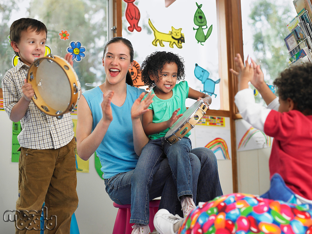 Children with teacher playing music in classroom